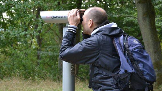 Foto: Høje sandbjerg - mand kigger i kikkert