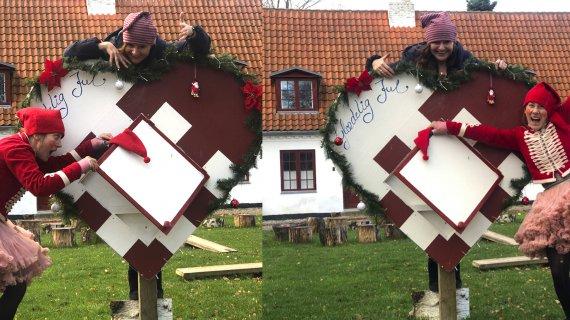 To nisser ved et stort julehjerte